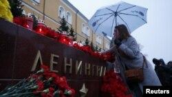 سوگواران برای کشتهشدگان در بخشی از دیوار کرملین در مسکو شمع روشن کردهاند