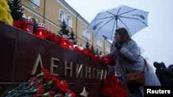 A woman lays flowers for the victims of the St. Petersburg blast by the Kremlin walls in Moscow.