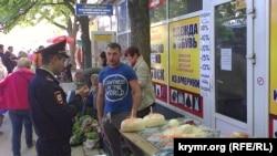 Поліцейський попереджає продавця соліннями про незаконність його торгівлі, Сімферополь