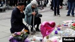 Еврейская женщина и мусульманин опалкивают жертв теракта в Манчестере. 24 мая 2017 года