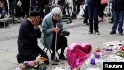 Мужчина и женщина оплакивают погибших на стадионе Манчестера, 24 мая 2017 года