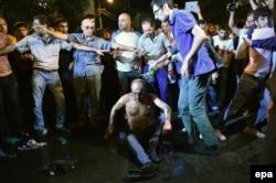 Участники акции протеста в Ереване помогают одному из своих товарищей через минуту после того, как он попытался совершить самосожжение