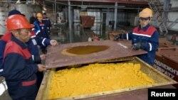 Рабочие уранового предприятия закрывают контейнер с оксидом урана. Южно-Казахстанская область, 24 апреля 2009 года. Иллюстративное фото.