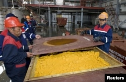 Жұмысшылар уран тотығы салынған контейнерді жауып жатыр. Оңтүстік Қазақстан облысы, Хорасан-1 уран кеніші, 24 сәуір 2009 жыл.