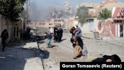 Гражданские в иракском городе Мосуле бегут в панике после авиаудара коалиции по позиции боевиков экстремистской группировки «Исламское государство» (ИГ).