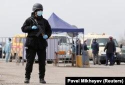 Карантин жарияланған Алматыда блокбекеттердің бірін күзетіп тұрған күштік құрылым қызметкері. 24 наурыз 2020 жыл.