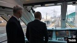 Președintele rus Vladimir Putin conduce trenul ce traversează podul peste strâmtoarea Kerci, 23 decembrie, 2019