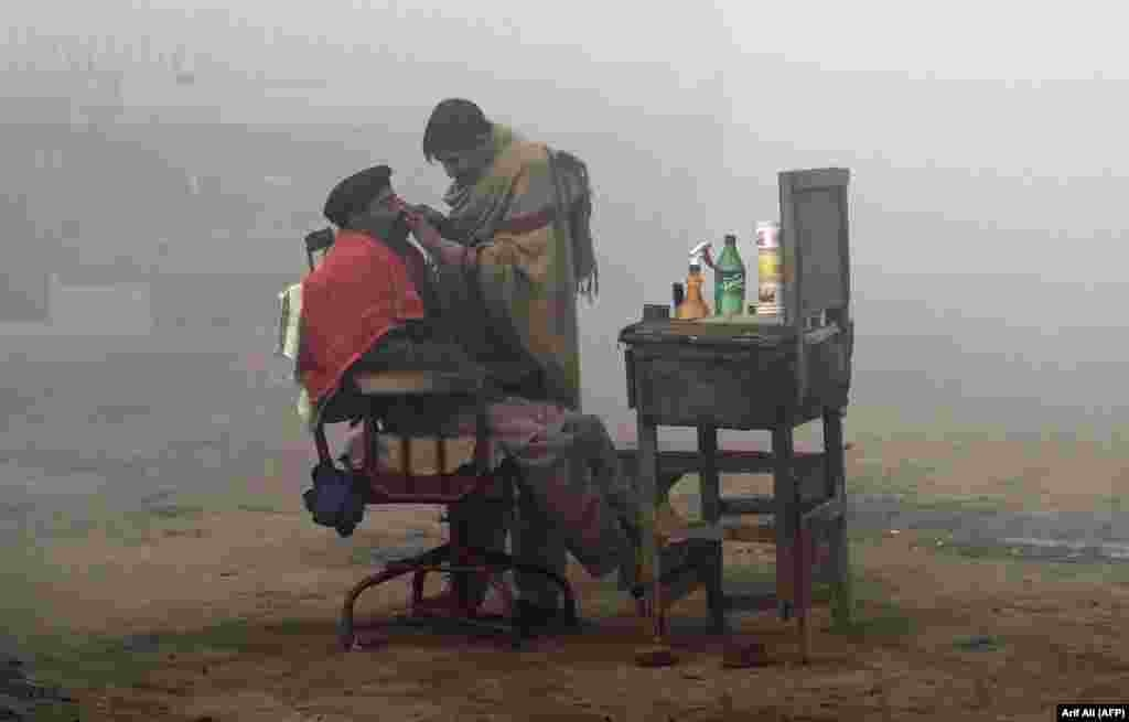 A Pakistani barber shaves a customer alongside a road amid heavy fog and smog conditions in Lahore. (AFP/Arif Ali)