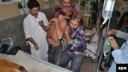 A supporter of Imran Khan, head of the Pakistan Tehrik-e-Insaf opposition party, victim of a stampede, gets medical treatment at a local hospital in Multan, Pakistan 10 October 2014.