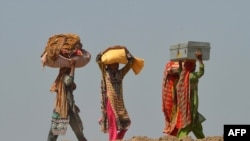Pakistanis affected by floods carry their belongings as they make their way to higher ground at a village in Jhang, in the central Punjab province, September 9, 2014.