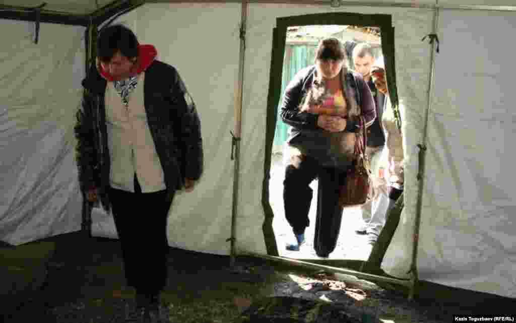Люди входят в палатку, установленную для жильцов сгоревшего дома в Турксибском районе Алматы.