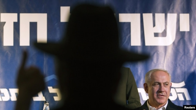 The silhouette of an ultra-Orthodox Jew at a convention with Prime Minister Benjamin Netanyahu (right) in Netanya, Israel, on January 13.