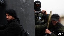 A Turkish fighter of the jihadist group Al-Nusra Front, bearing the flag of Al-Qaeda on his jacket (center), holds position with comrades in the village of Aziza, on the southern outskirts of Aleppo, in April.