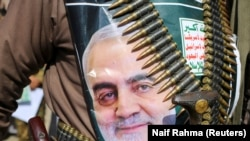 A supporter of the Houthis has a poster attached to his waist of Soleimani, during a rally to denounce the U.S. killing.