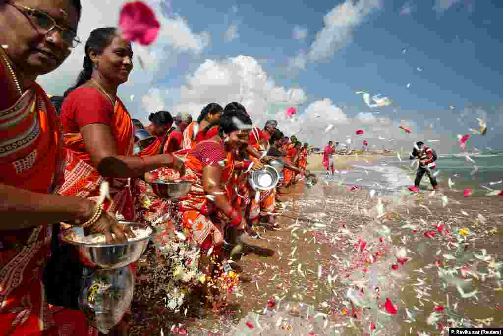 Women scatter flower petals in the waters of the Bay of Bengal during a prayer ceremony for the victims of the 2004 tsunami on the 15th anniversary of the disaster, at Marina beach in Chennai, India, on December 26. (Reuters/P. Ravikumar)