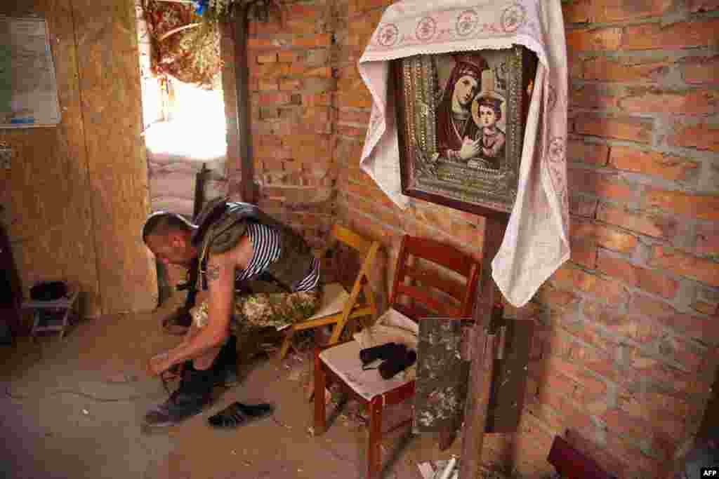 A Ukrainian serviceman laces up his boots in an Orthodox church destroyed after helling between Ukrainian forces and pro-Russian separatists in the village of Pisky in the Donetsk region. (AFP/Oleksandr Ratushniak)