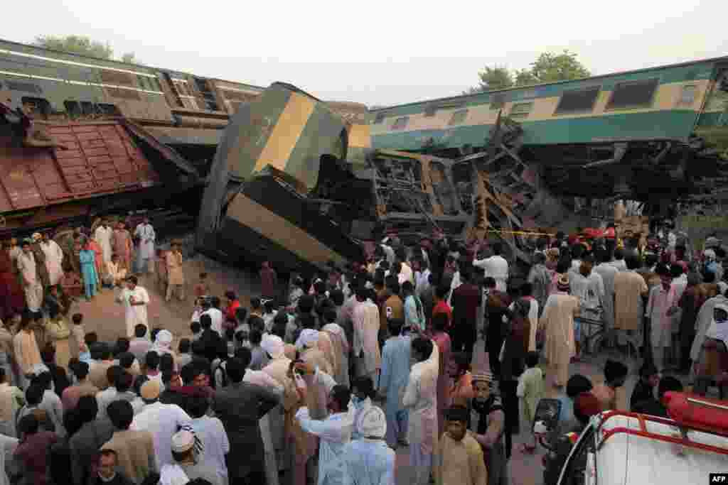 Pakistani bystanders gather at the site of a collision between an express train and a freight train on the outskirts of Multan. At least six people were killed and more than 100 injured. Railway officials blamed the accident on the passenger train engineer, saying he failed to heed a red signal that went up after the freight train had stopped. The freight train stopped so the driver could remove the body of a man who tried to cross the track and got crushed to death. (AFP/SS Mirza)