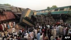 Pakistani bystanders gather at the site of the collision of two trains on the outskirts of Multan on September 15.