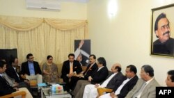 Pakistani Prime Minister Yousaf Raza Gilani (right of center) speaks with leaders of MQM during a meeting at their headquarters in Karachi on January 7.