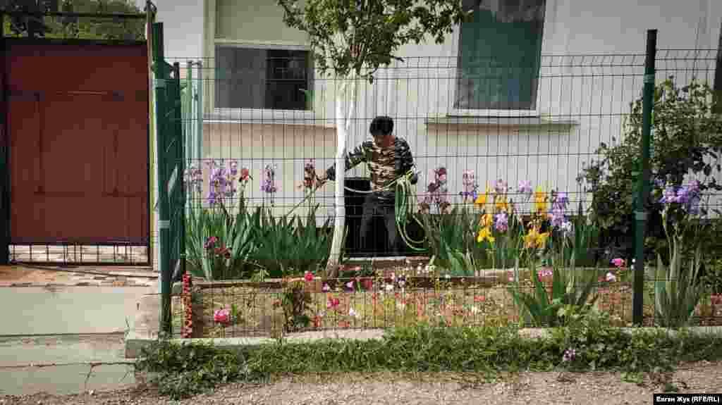 У частного дома мужчина поливает цветы в палисаднике