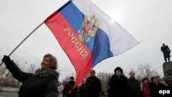 A woman holds a Russian flag on a central square in Sevastopol, the Crimean capital, on March 16.