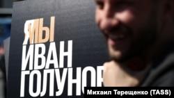 """""""Медуза"""" тілшісі Иван Голуновтың есімі жазылған постер жанында тұрған азамат."""