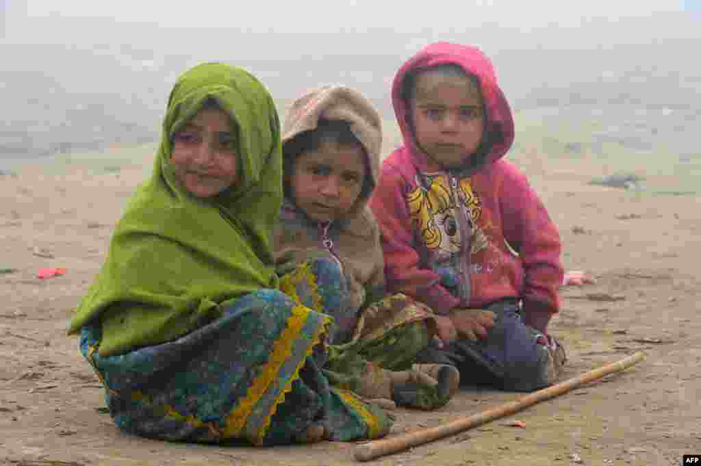 Young homeless children sit on the ground during a foggy day in Peshawar, Pakistan. (AFP/A. Majeed)