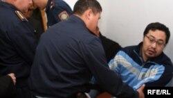 Полицейские уводят оппозиционного активиста Ермека Нарымбаева из зала суда. Алматы, 14 мая 2010 года.