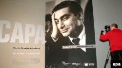 Фотограф снимает афишу ретроспективной выставки Роберта Капы