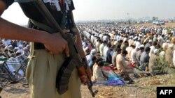 افغان کډوال د پوليسو په پېره کې مونځ کوي.