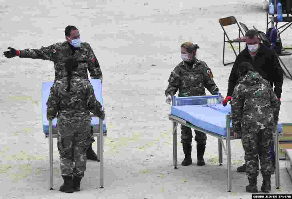 Soldați macedoneni amplasează paturi pentru un nou spital mobil, amplasat lângă Clinica Universitară pentru Boli Infecțioase din Skopje, pe 31 martie.