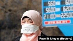 Ақша айырбастайтын орынның қасынан өтіп бара жатқан маска таққан әйел. Алматы, 16 наурыз 2020 жыл.