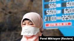 Женщина в маске рядом с электронным табло пункта обмена валют в Алматы. 16 марта 2020 года.