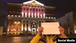 Журналист Филипп Киреев прикрывается бумажкой на фоне здания московской мэрии