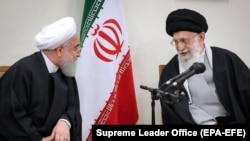 File - Iranian supreme leader Ayatollah Ali Khamenei (R) speaks with President Hassan Rouhani during a meeting with members of Iranian Assembly of Experts in Tehran, March 14, 2019