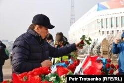 Активист Жанболат Мамай возлагает цветы к монументу Независимости в Алматы. 16 декабря 2019 года.