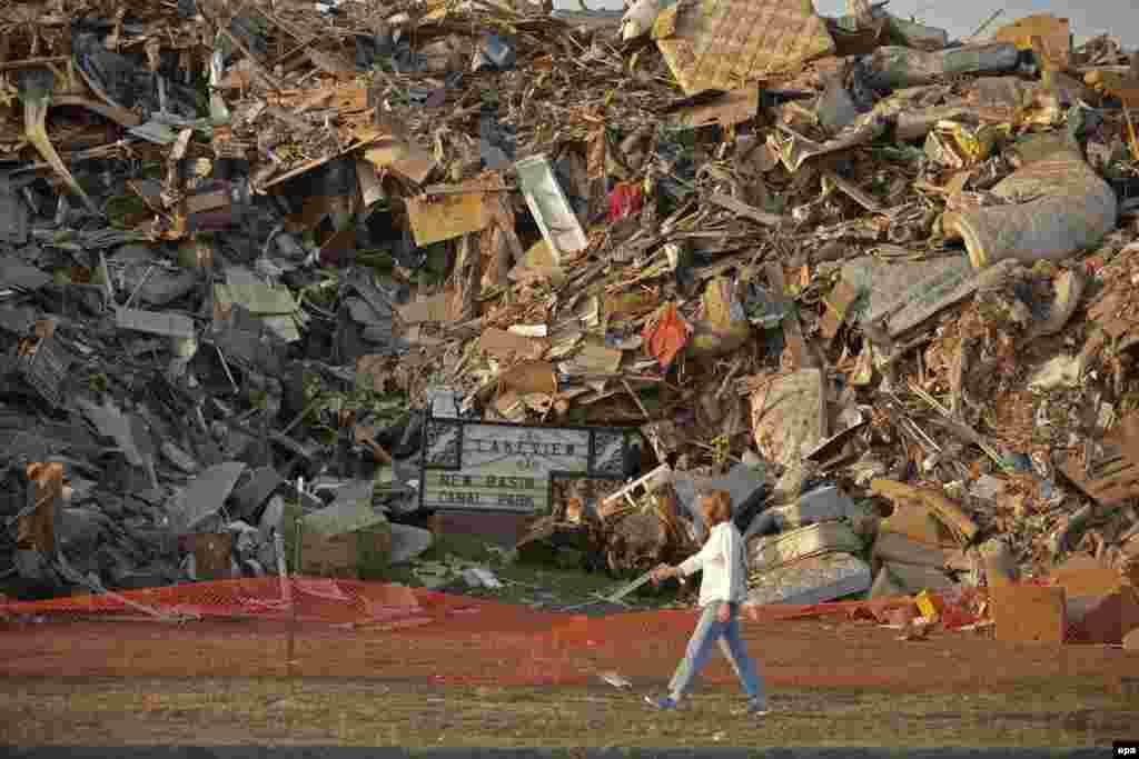 A woman walks past a mountain of debris filling entire city blocks from destroyed homes in the Lakeview section of New Orleans.