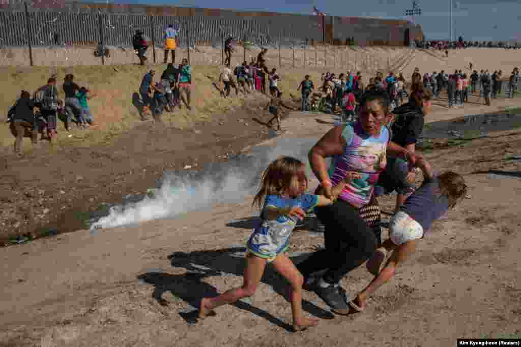 Maria Meza, a 40-year-old migrant woman from Honduras, runs away from tear gas with her 5-year-old twin daughters Saira Mejia Meza (left) and Cheili Mejia Meza (right) in front of the border wall between the United States and Mexico, in Tijuana, Mexico, November 25, 2018.(Reuters/Kim Kyung-hoon)