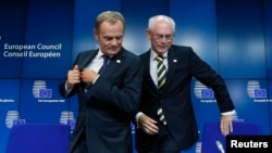 Newly elected European Council President Donald Tusk (left) holds a news conference with outgoing predecessor Herman Van Rompuy during a EU summit in Brussels on August 30.
