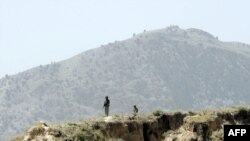 Pakistani soldiers stand guard on a mountain ridge in Pakistan's tribal district of Mohmand Hills.