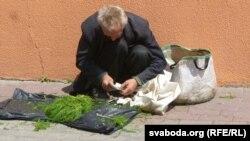 Пэнсіянэр гандлюе зелянінай каля сьцяны Камароўскага рынку