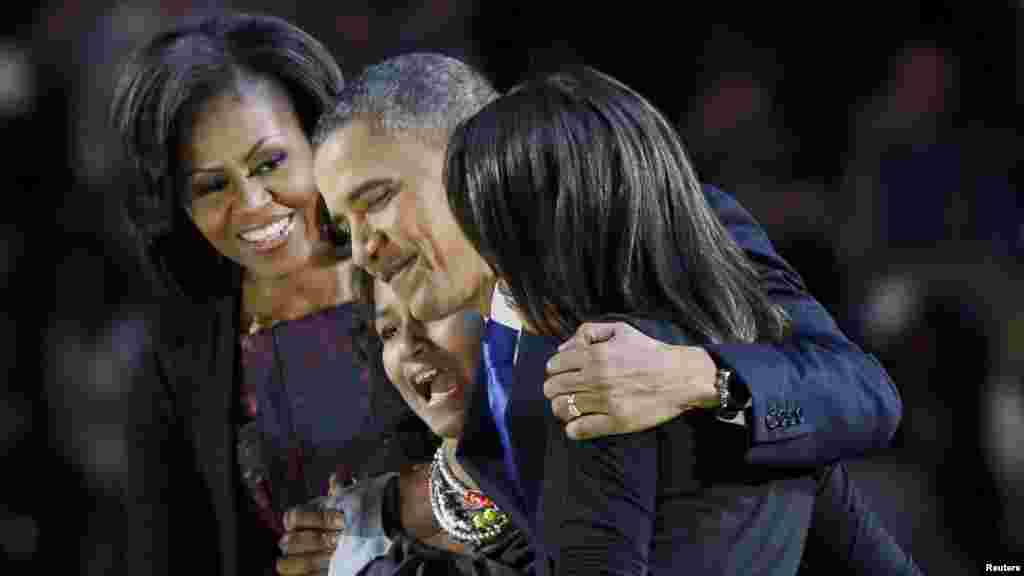 President Barack Obama hugs his daughters, Malia and Sasha, as First Lady Michelle Obama looks on during his election night victory rally in Chicago.