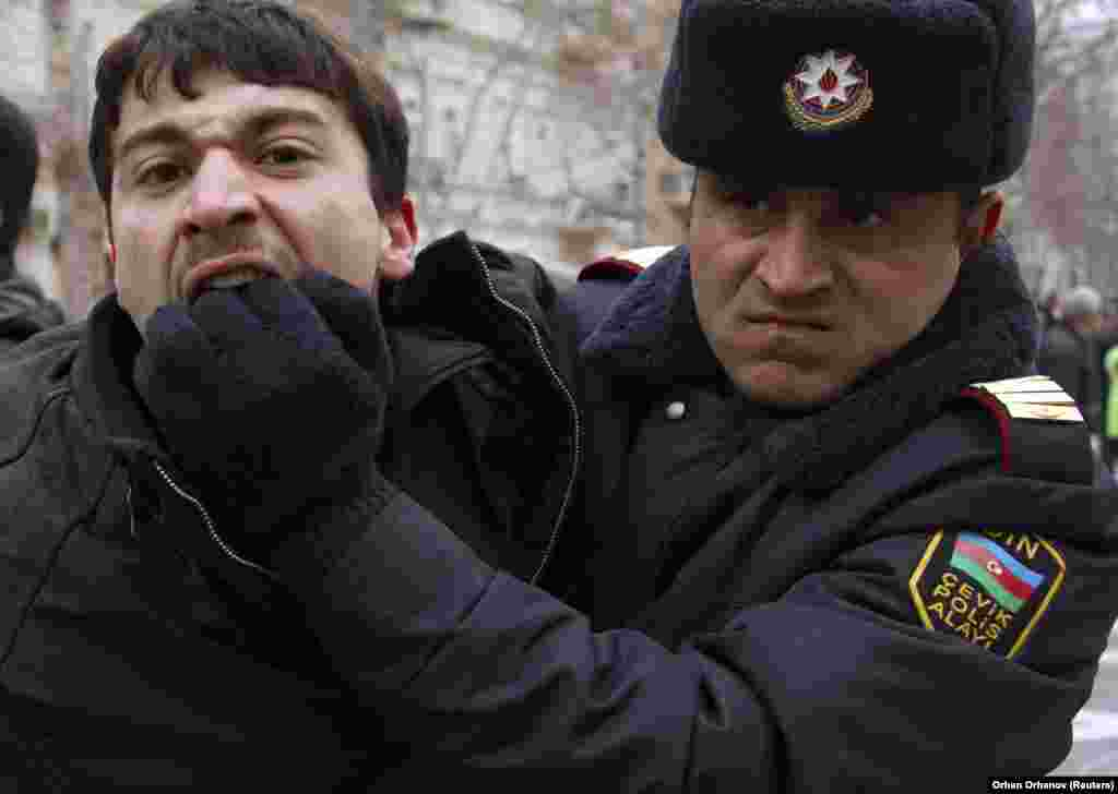 A policeman detains an opposition activist in Baku in 2011. Police crackdowns have muted dissent in the past, but with recent protests springing up spontaneously in small towns throughout the country the current unrest may be the harbinger of troubled times to come.