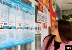 A voter reads information about the candidates for parliament at a polling station in the town of Belovodsk on September 30.