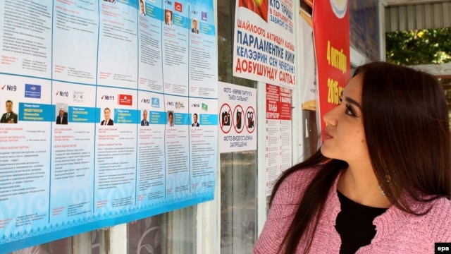 A Kyrgyz woman reads information about the candidates for parliament at a polling station in the town of Belovodsk, in Kyrgyzstan's Chui Province.