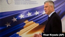 President Hashim Thaci stands in front of a banner marking the 10th anniversary of Kosovo's independence during an interview with the Associated Press in Pristina on February 14.