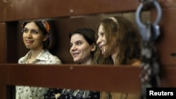 Pussy Riot members Nadezhda Tolokonnikova (from left to right), Yekaterina Samutsevich, and Maria Alyokhina look out from the defendents' cell in a court in Moscow.