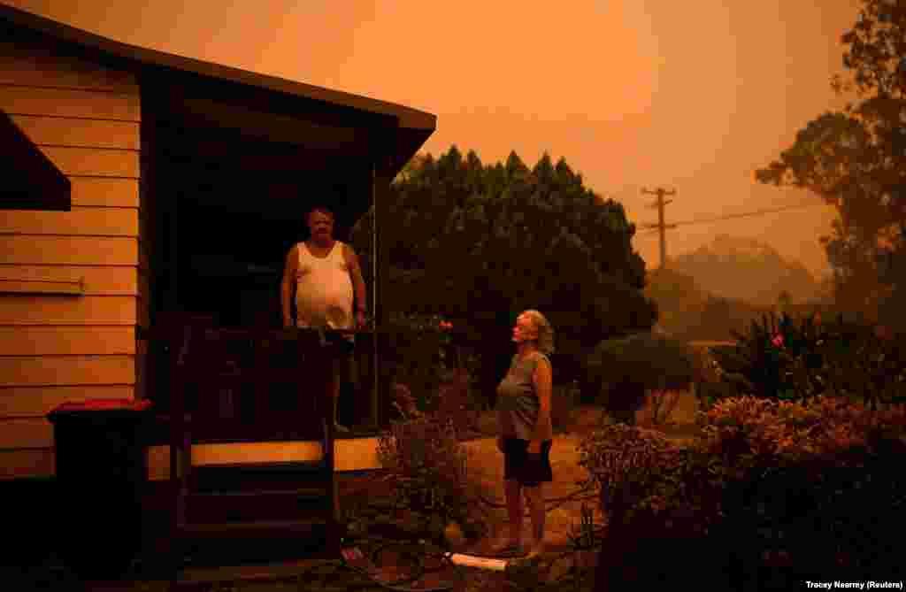 Nenci i Brajan Alen koriste baštenska creva da nakvase kuću i vrt oko nje u Nouri