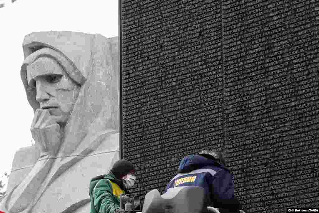 Workers clean the names of World War II soldiers at the Glory Monument in Novosibirsk on April 13, 2020.