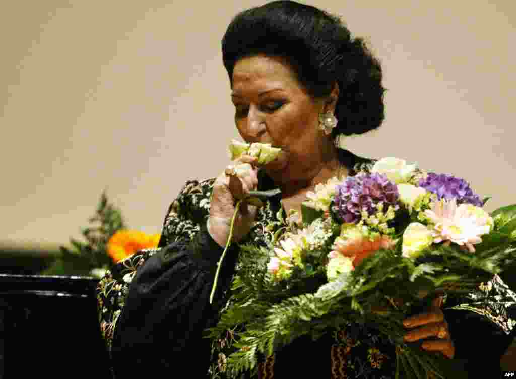 Montserrat Caballe sniffs a flower on stage after performing on October 3, 2005, in the Gewandhaus concert hall in Leipzig.